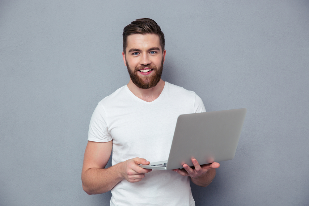 Portrait of a smiling casual man holding laptop over gray background-1